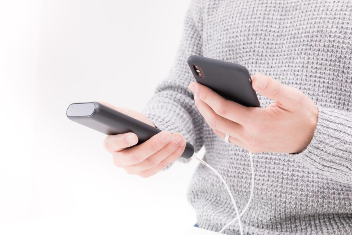 モバイルバッテリーを利用しつつスマホを操作する男性